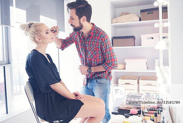 Männlicher Make-up-Künstler trägt Eyeliner auf Modell für Fotoshooting auf