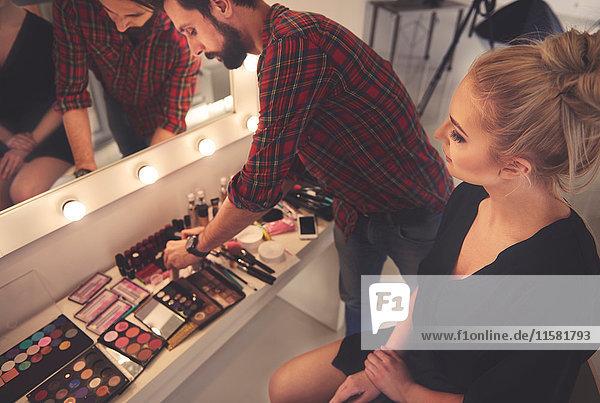 Männlicher Make-up-Künstler wählt Make-up für Fotoshooting