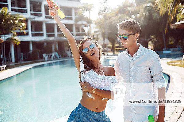 Junges Paar hält Wasserpistole am Pool hoch  Koh Samui  Thailand