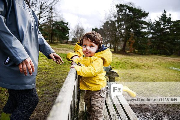 Kleiner Junge mit Mutter in gelbem Anorak auf Parkbank