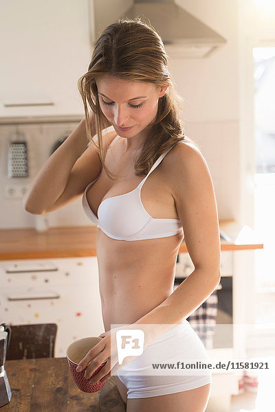 Beautiful woman in kitchen wearing bra and knickers
