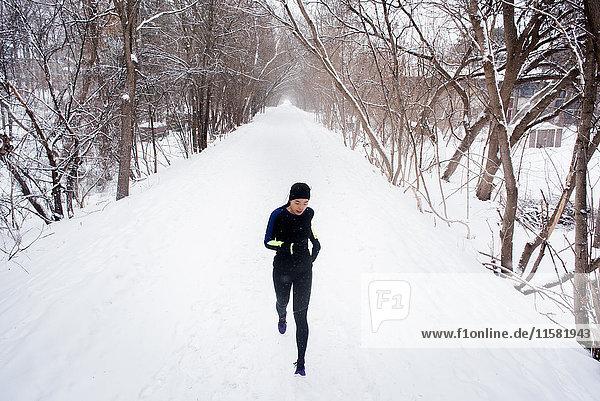 Junge Läuferin mit Strickmütze läuft in einem von Bäumen gesäumten  schneebedeckten Park