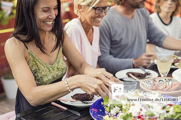 Fröhliche Menschen sitzen am Esstisch während der Gartenparty im Hinterhof
