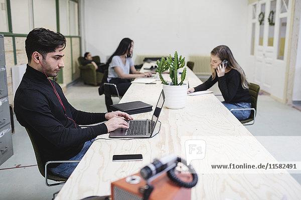 Die Unternehmer mit Laptops und Smartphone am Schreibtisch im Kreativbüro