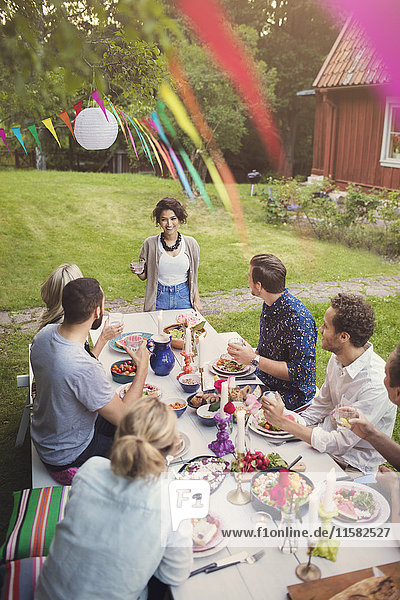 Happy woman talking to friends at table in garden party
