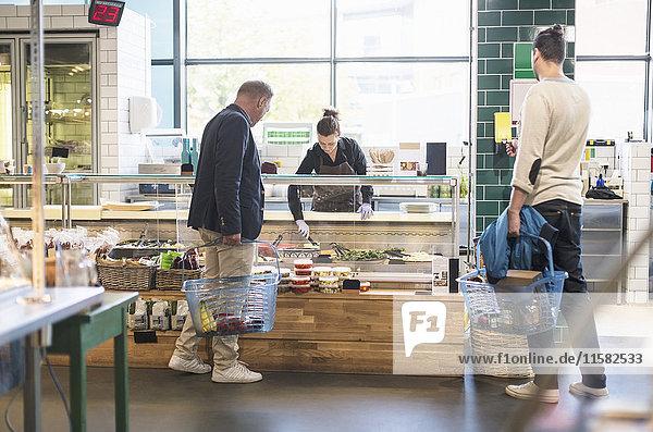 Mann kauft Lebensmittel bei Verkäuferin im Bio-Supermarkt ein