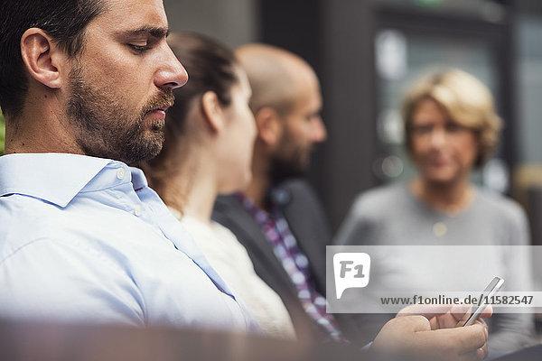 Seitenansicht des Geschäftsmannes per Handy durch Kollegen im Bürohof