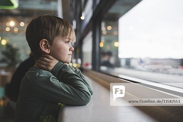 Nachdenklicher Junge lehnt sich an den Tisch am Fenster des Restaurants. Nachdenklicher Junge lehnt sich an den Tisch am Fenster des Restaurants.