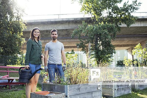 Porträt eines glücklichen mittleren Erwachsenenpaares mit Gießkanne im Stadtgarten