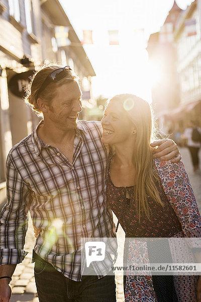 Fröhliches Paar mit Armen  das bei Sonnenuntergang in der Stadt spazieren geht.