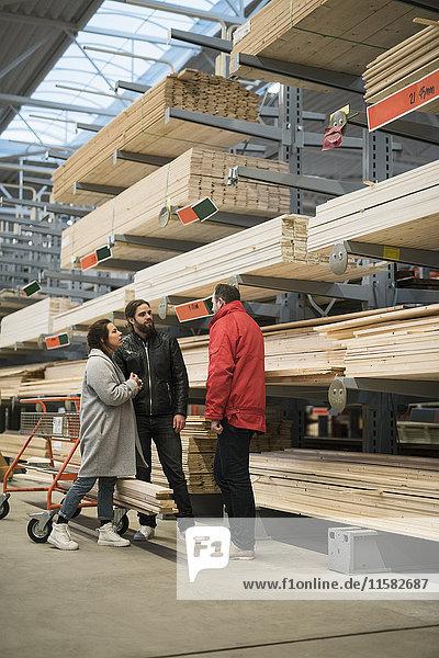 Kunden und Verkäufer stehen neben Holzbrettern in den Regalen des Baumarktes.