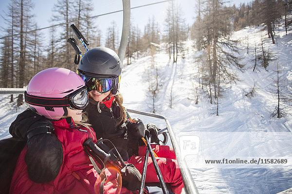 Glückliche Mutter und Tochter reisen im Skilift