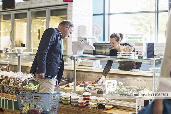 Verkäuferin hilft reifem Mann beim Einkauf von Lebensmitteln im Supermarkt