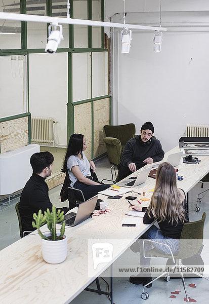 Vier Unternehmer  die am Schreibtisch im kreativen Büro diskutieren