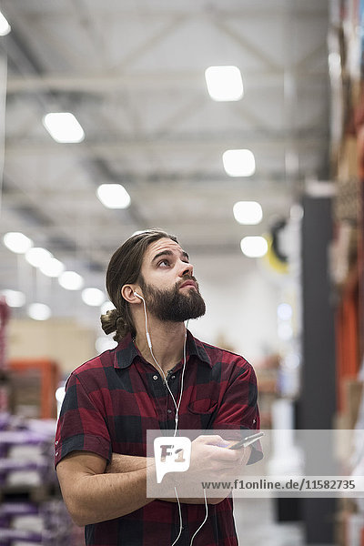Male customer looking up while listening music through smart phone at hardware store