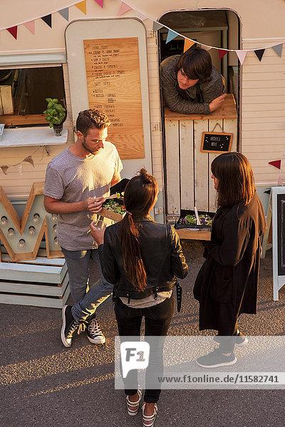 Großer Blickwinkel auf Kunden und Food-Truck-Besitzer auf der Straße
