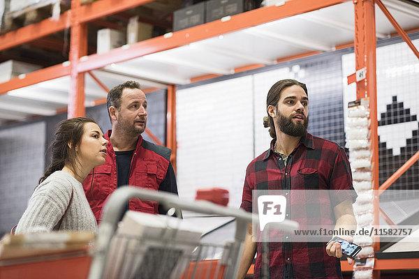 Verkäufer und Paar schauen weg  während sie im Baumarkt stehen.