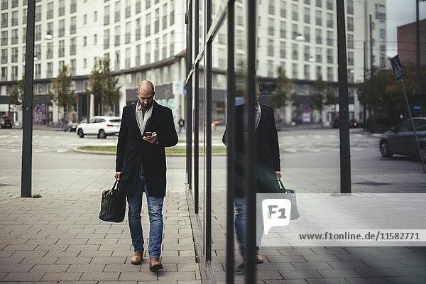 Volle Länge des Geschäftsmannes mit dem Handy beim Gehen auf dem Bürgersteig in der Stadt