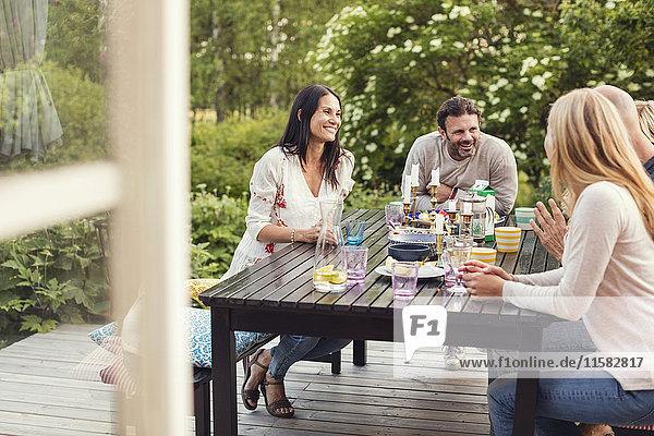 Glückliche Familie und Freund sitzen am Esstisch im Hinterhof