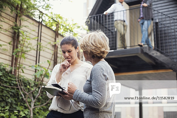 Geschäftsfrauen diskutieren über digitales Tablett im Bürohof