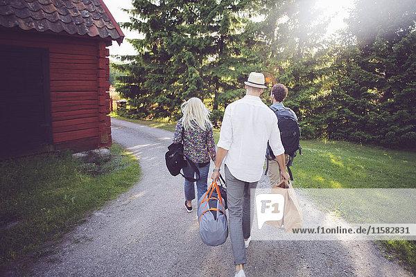 Rückansicht von Freunden mit Gepäck  die auf einem Fußweg durch die Hütte gehen.