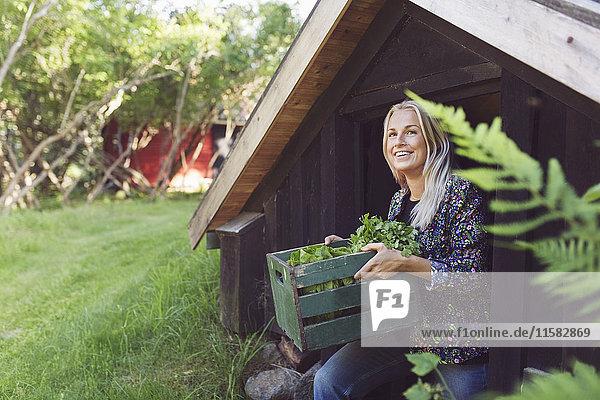 Lächelnde Frau mit Gemüsekiste beim Verlassen der Hütte