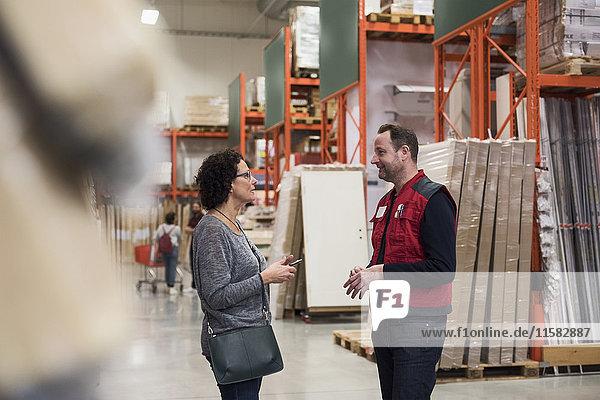 Frau im Gespräch mit dem Verkäufer  während sie ein Smartphone im Baumarkt hält.