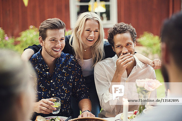 Smiling woman standing with friends at table in garden party