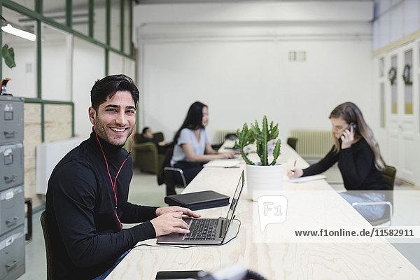 Porträt eines glücklichen jungen Mannes am Schreibtisch mit Kollegen im Hintergrund