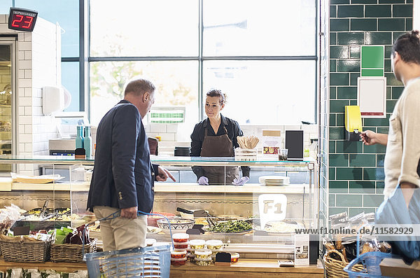 Reifer Mann kauft Lebensmittel bei Verkäuferin im Supermarkt ein