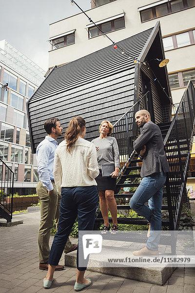 Geschäftsleute diskutieren außerhalb des Blockhauses auf dem Bürohof
