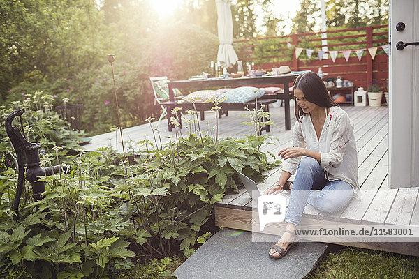 Hohe Winkelansicht der Frau  die den Laptop benutzt  während sie auf der Terrasse im Hinterhof auf der Diele sitzt.