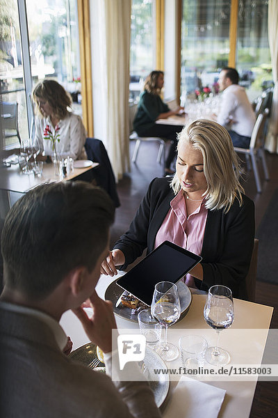 Businesswoman discussing with male colleague while showing digital tablet during meeting at restaurant