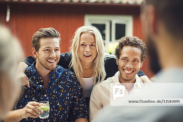 Smiling woman standing with friends at garden party