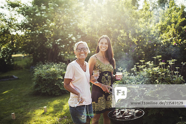 Portrait of happy women standing by barbecue grill at back yard on sunny day