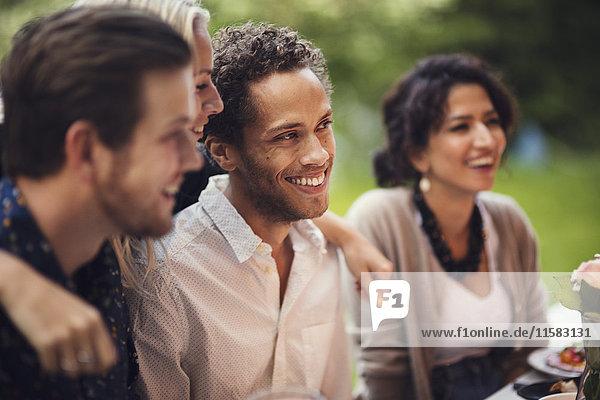 Lächelnde Männer und Frauen beim Gartenfest