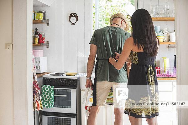 Rückansicht der Frau mit Schürzenknoten für den Mann in der Küche zu Hause