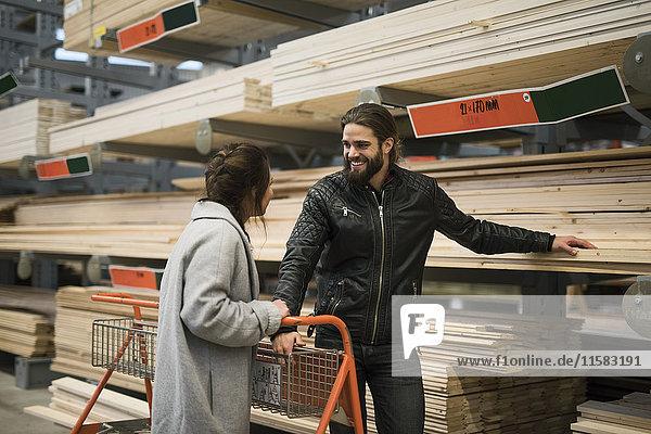 Lächelnder Mann steht mit Frau an Holzbrettern in den Regalen des Baumarktes