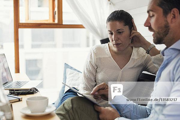 Mittlere erwachsene Geschäftsfrau mit männlichem Kollegen mit digitalem Tablett im Büro