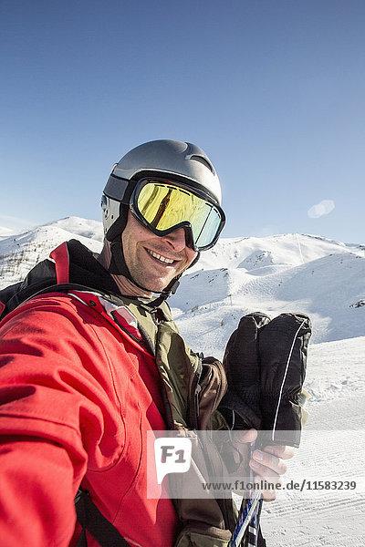 Lächelnder Mann in Skibekleidung steht auf schneebedecktem Feld gegen den klaren Himmel.