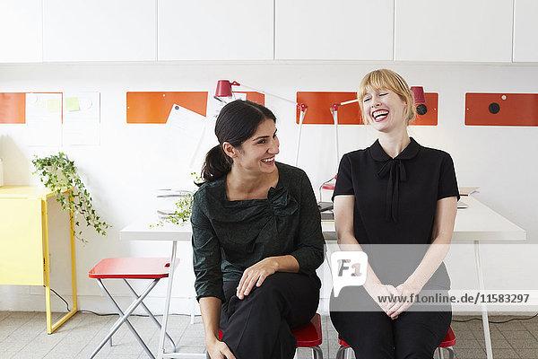Fröhliche Geschäftsfrauen  die auf Stühlen im Büro sitzen