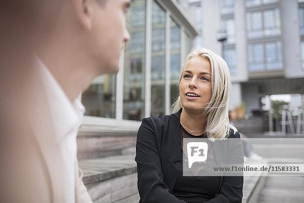 Glückliche blonde Geschäftsfrau im Gespräch mit einem männlichen Kollegen in der Stadt