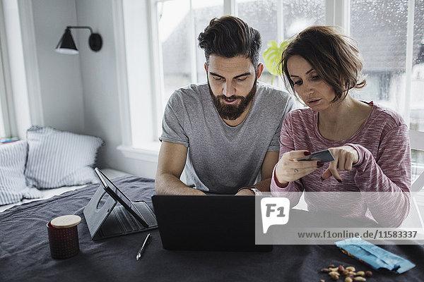 Frau hält Kreditkarte  während der Mann den Laptop auf dem Tisch zu Hause benutzt.