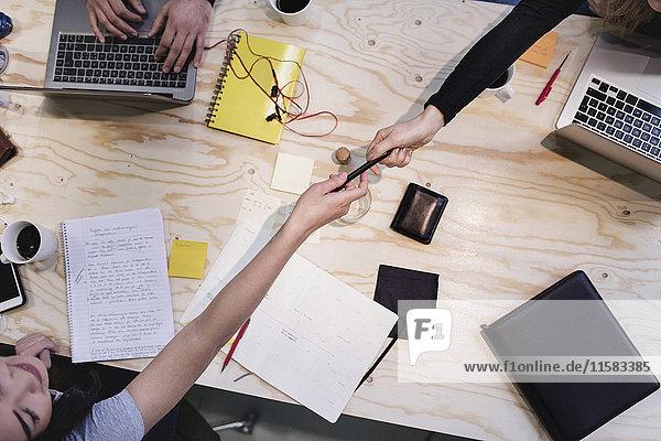 Direkt über der Aufnahme der Frau  die dem Kollegen am Holzschreibtisch einen Stift gibt.