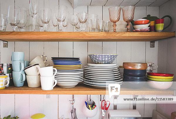 Geschirr und Trinkgläser in den Regalen der heimischen Küche