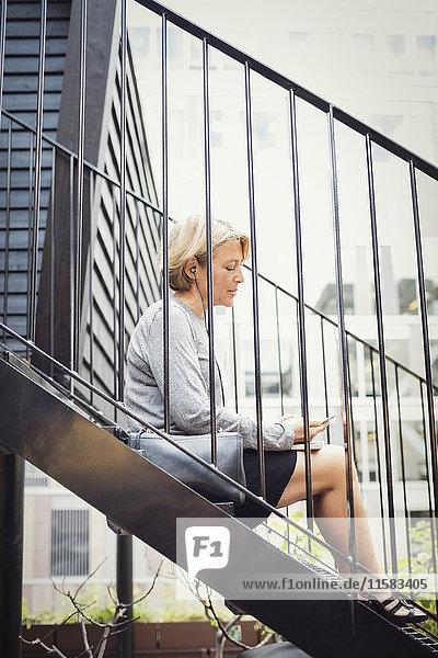 Seitenansicht der Geschäftsfrau mit Smartphone auf der Treppe im Bürohof
