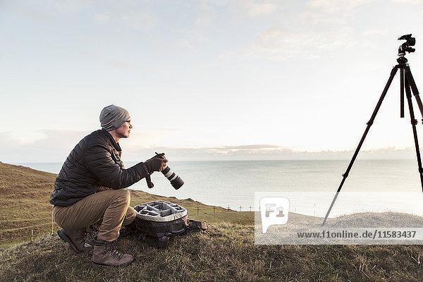Seitenansicht des Wanderers  der weg schaut  während er die Spiegelreflexkamera am Berg auf dem Meer gegen den Himmel hält.