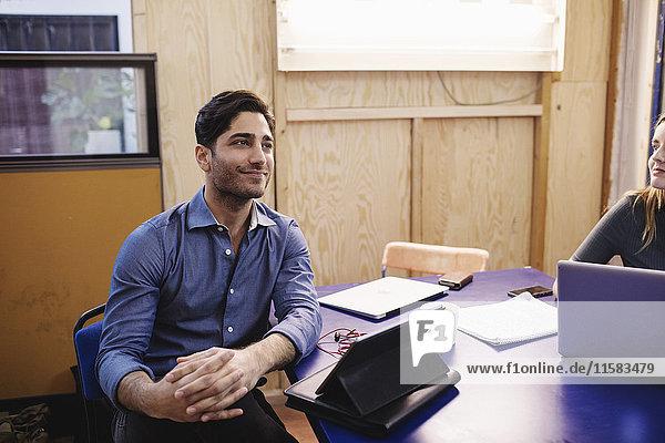 Lächelnder junger Mann schaut weg  während er im Büro am Schreibtisch sitzt.