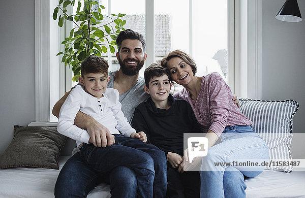 Glückliche Familie sitzt auf dem Sofa im Wohnzimmer zu Hause