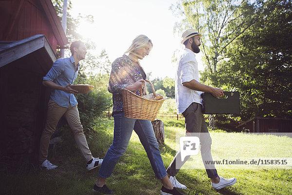 Glückliche Freunde halten Kiste und Container  während sie gegen die Hütte auf der Wiese laufen.